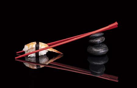 hashi: Shrimp Sushi with chopsticks red isolated over black background