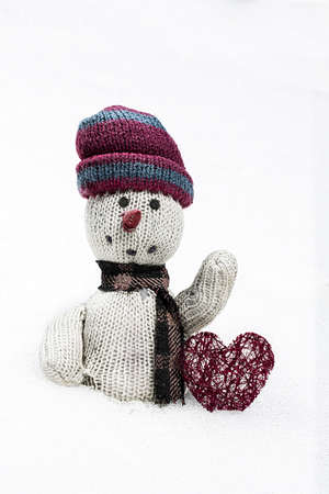 rags: old rag doll in the snow with a red heart on white background