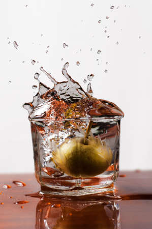 Water splash into a glass with a decorative pear