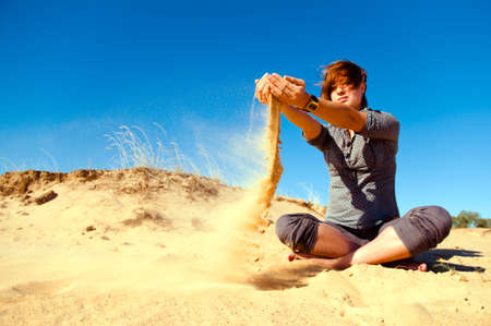 Woman playing with sand and wind Stock Photo