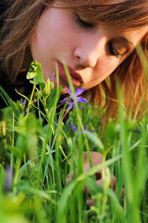 The girl bent over the ground to see the flower Stock Photo - 7981168