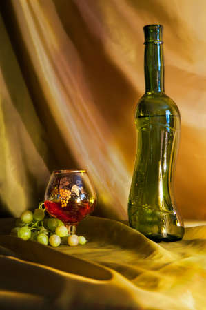 A glass of wine and grapes are close to a bottle of wine