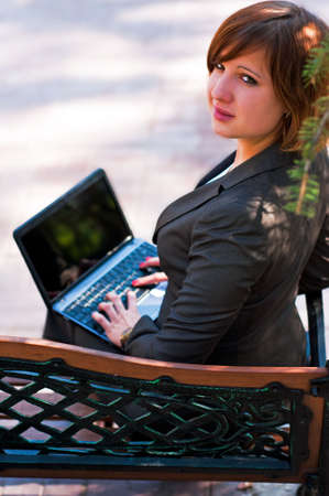 Young girl with laptop in the park Stock Photo