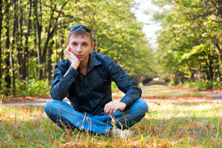 The young guy in good mood has a rest on a lawn