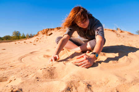 The girl sits on sand and enjoys the nature Stock Photo - 8029837