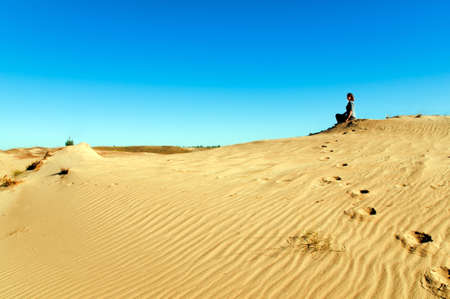 Young girl relaxation in desert under blue sky. Reditation
