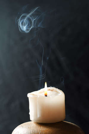 A single candle, with a beautiful smoke trail coming from it
