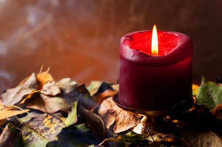 Lit candle sitting in dried leaves Stock Photo