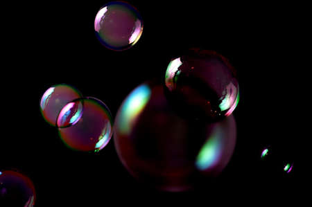 Seven soap bubbles isolated on black