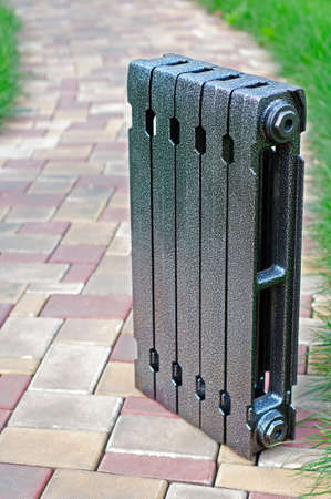 Radiator with thermostat stand beside a young green grass Stock Photo