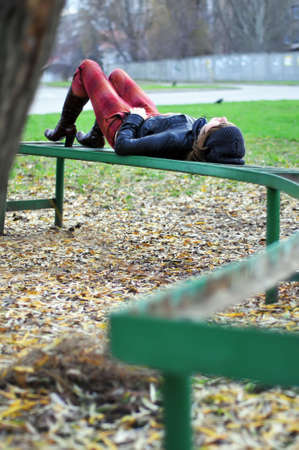 A young girl lies on the old bench on the edge of the park. Autumn