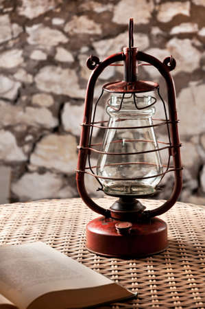 Kerosene lamp stands on a wicker table, next to the book in a dark room    photo