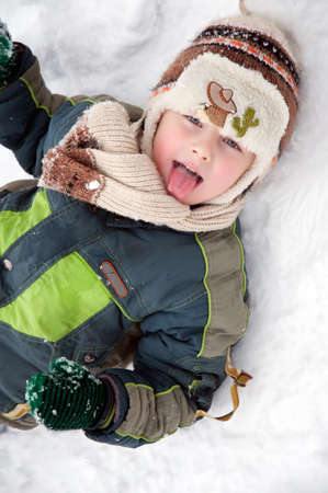 The happy boy lies on snow and puts out the tongue Stock Photo