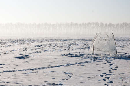 Ice-hole in the center of a frozen lake Stock Photo