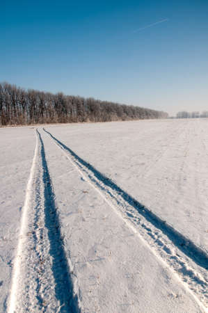 Landscape with a trace of the aircraft in the clear sky and a long snowy country road