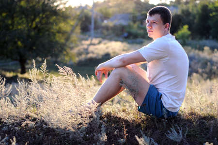 Young guy sits on a grass, a sun lights up him.