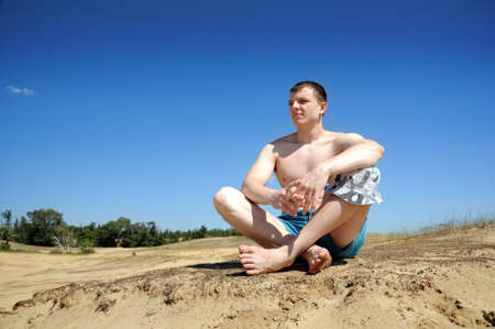 Guy sitting on the sand in the lotus position. Summer hot sun