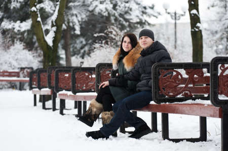Young couple relaxing in a snow-covered park on weekends