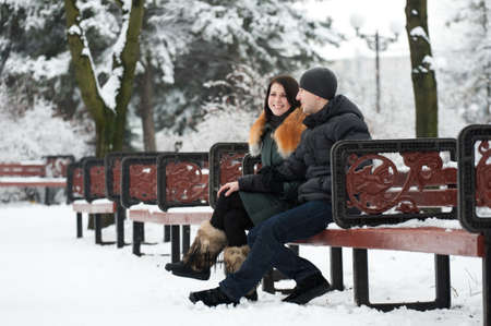 Young happy couple relaxing in a snow-covered park on weekends Stock Photo