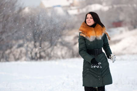 Young girl throws a snowball far. Rest in park