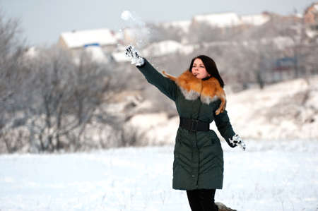 Young woman highly throws a snowball