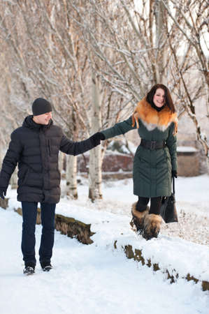 Happy young couple walking in the snow-covered streets