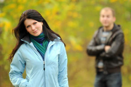 Couple posing in outdoor. Young woman in focus