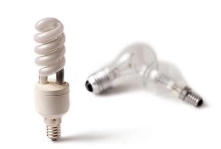 Energy saving lightbulb in focus and classic lightbulb. Isolate