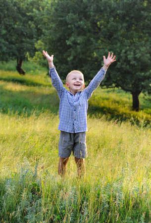 Happy little boy holding hands up in outdoor Sun backlit