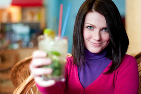 Young beautiful woman offers a cocktail photo