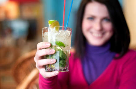 Young beautiful woman offers a cocktail - mojito Stock Photo