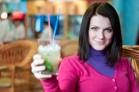 Young beautiful woman offers a cocktail