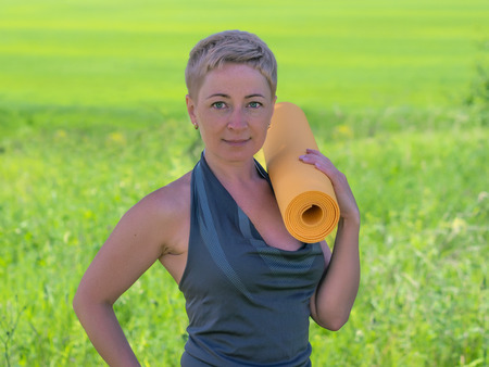 only women: Mature Woman Holding Rolled Up Exercise Mat Outdoors Stock Photo