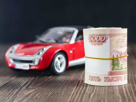 thousandth: a roll of five thousandth rubles notes on background of toy car on dark wood table
