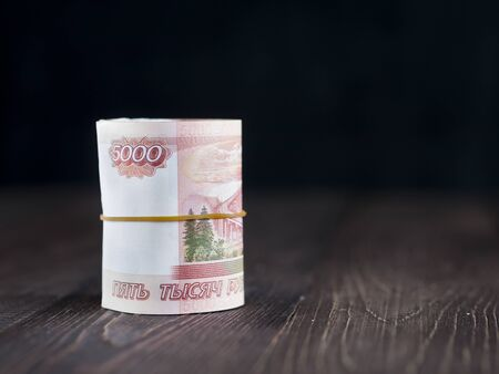 thousandth: roll of five thousandth rubles banknotes on dark wooden background