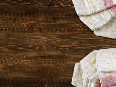 Japanese disposable diapers on dark wooden background with copy-space. Flat lay