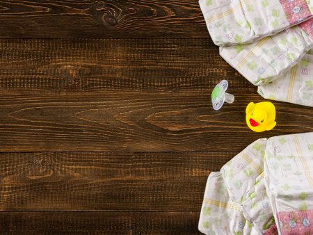 12 18 months: Japanese disposable diapers and dummy and rubber duckling on dark wooden background with copy-space. Flat lay