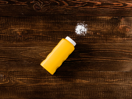 talcum: Spilled baby talcum powder on dark wooden background. Flat lay Stock Photo