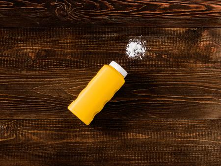 talc: Spilled baby talcum powder on dark wooden background. Flat lay Stock Photo