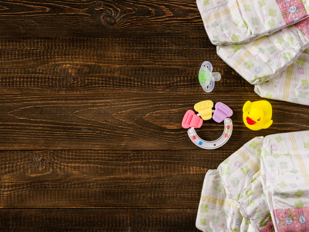 12 18 months: Japanese disposable diapers, teether, dummy and rubber duckling on dark wooden background with copy-space. Flat lay