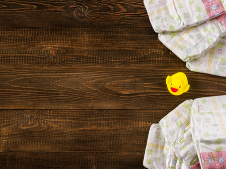 12 18 months: Japanese disposable diapers and the rubber duckling on dark wooden background with copy-space. Flat lay Stock Photo