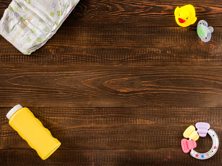 12 18 months: disposable diaper, teether, dummy, baby powder and rubber duckling on dark wooden background with copy-space. Flat lay