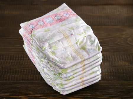 Stack of disposable diapers on a wooded background 스톡 콘텐츠
