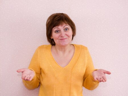shrug: An unsuspecting mature woman shrugs and smiling. Shrug of helplessness
