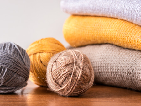 knitwear: skeins of yarn and knitwear on wooden table