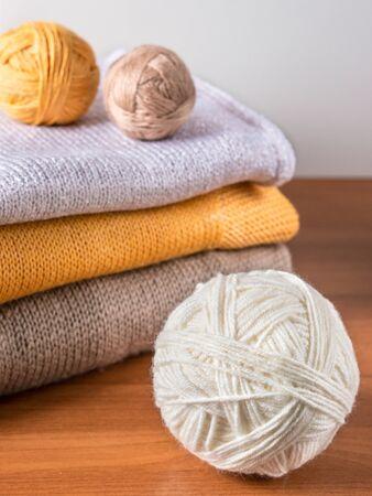 knitwear: white skein of yarn on background of knitwear and yarn