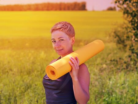 only mature women: Mature Woman Holding Rolled Up Exercise Mat Outdoors Stock Photo