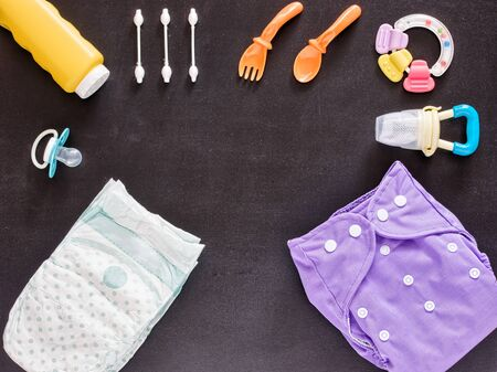 nappies: Baby set of cloth diaper, disposable diaper, baby powder, tither, cotton buds, spoons, soother and nibbler on dark background with copy space. Top view or flat lay