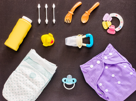 nappies: Baby set of cloth diaper, disposable diaper, baby powder, tither, cotton buds, spoons, soother, nibbler and rubber duckling on dark background. Top view or flat lay Stock Photo