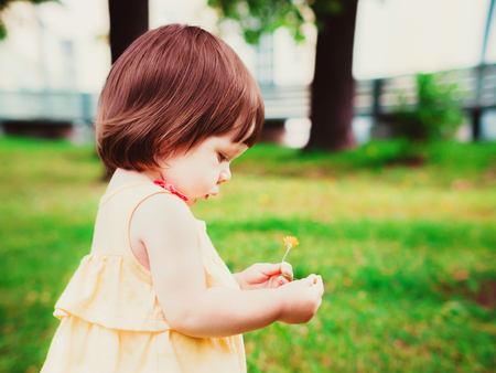 year profile: Little Baby Girl Portrait in profile outdoor. Cute Child over nature background. Adorable one year old baby with flower in hands